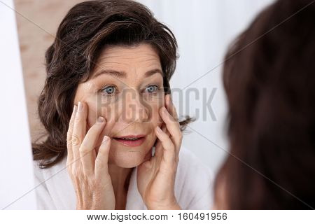 Senior woman touching face in front of mirror, closeup