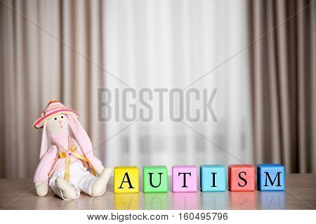 Wooden cubes with doll on curtains background. Autism concept