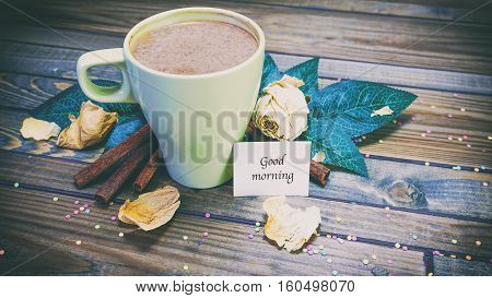 Cup Of Cinnamon And Coffee On A Wooden Background, Word On Paper