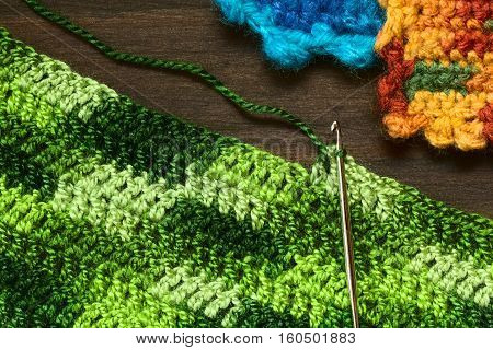 Crochet handicraft making a place mat out of green yarn with a pattern of double stitches using a metal crochet hook or needle photographed overhead with natural light