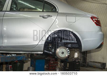 silver car with the removal of the wheels on the lift