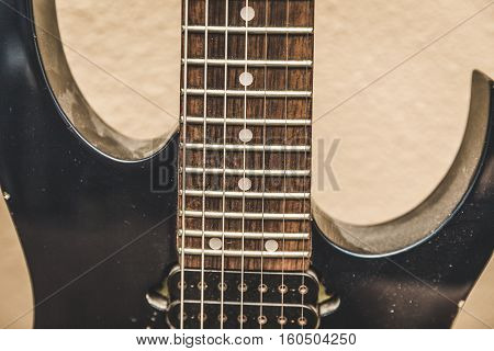 Seven string guitar close up covered in dust