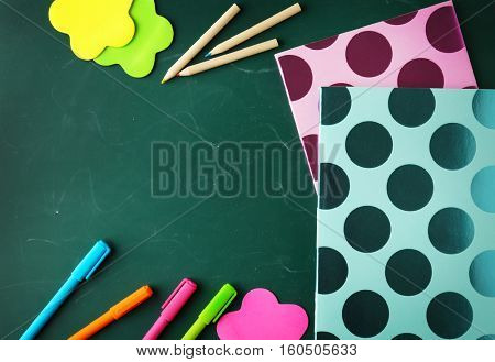 Colorful school stationery on green background, top view