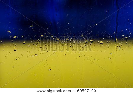 Raindrops on window glass on blue and yellow background in colors of the Ukrainian national flag