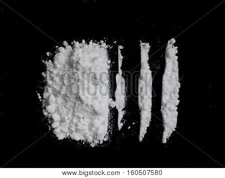 Cocaine drug powder and lines on black background