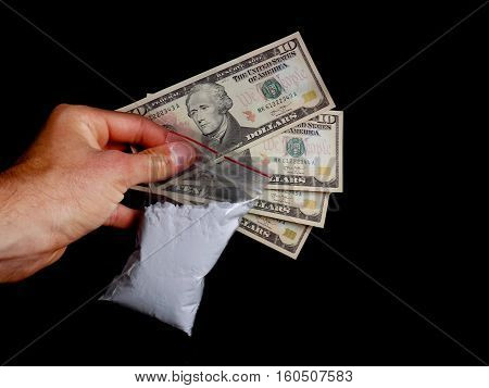 Drug dealer holding bag with cocaine drug powder and dollar bills money, men selling drugs junkie on black background