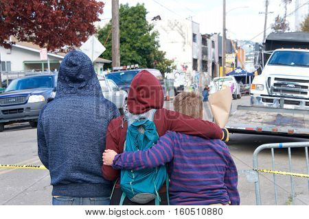 Oakland CA - December 06 2016: Friends and family stand watching in the aftermath of the