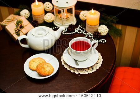 Close up of cookies on white plate and cup of fruit tea on wooden table in cafe. Decoration for Christmas with candles.