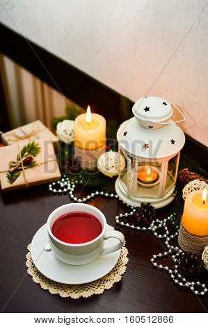 Close up of cup of fruit red tea on wooden table in cafe. Decoration for Christmas with candles and present.