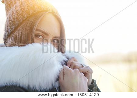 Gorgeous shy girl hiding behind the white fur of her jacket on a sunny winter day - Stunning brunette with a phone in her hand