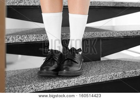 Feet of schoolgirl in uniform sitting on stairs