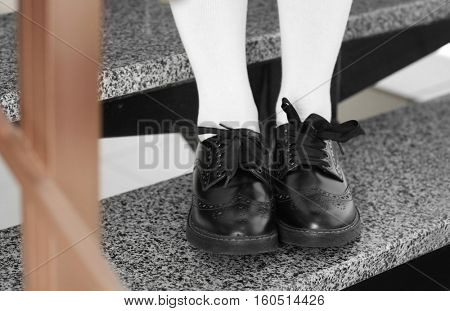 Feet of schoolgirl in uniform sitting on stairs, close up view
