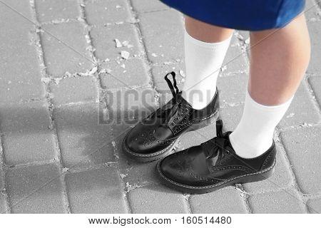Feet of schoolgirl in uniform outdoors