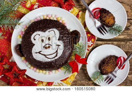 Funny children's cake monkey and chocolate pinecones on a festive Christmas table
