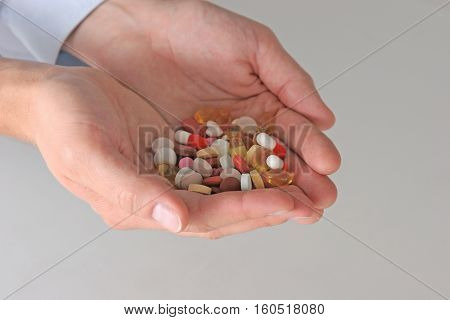 Hand of doctors holding many different pills.