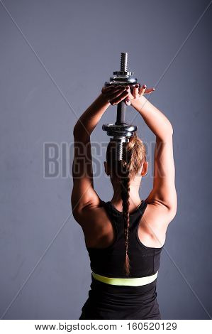 Athletic woman doing a fitness workout with Barbel weights for her back and arm muscles sit on the box