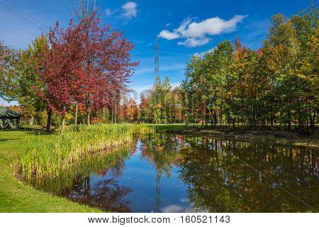 Shining day in French Canada. Charming oval pond in the picturesque park. Concept of recreational tourism. Autumn foliage reflected in clear water of the pond