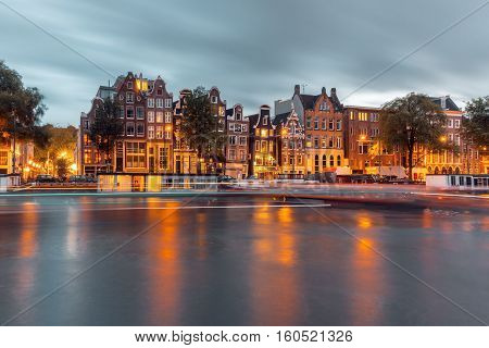 Amsterdam canal Amstel with typical dutch houses, houseboat and luminous track from the boat during twilight blue hour, Holland, Netherlands.