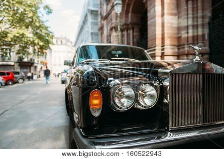 PARIS FRANCE - SEP 12 2016: Headlight and logotype of a exclusive Luxury Rolls-Royce car limousine parked in city during fashion wedding vip event waiting for passenger. Rolls-Royce Limited is a British car-manufacturing and later aero-engine manufacturin