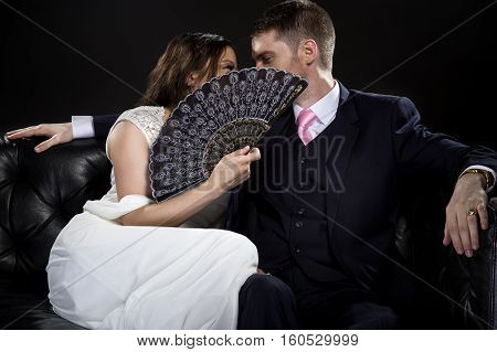 Engaged couple in a relationship hiding behind a fan kissing or whispering and wearing retro noir style suit and dress. Privacy concept.