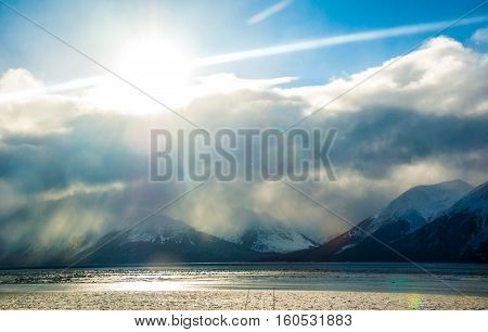 Sun Rays beam from clouds opening up over Bay of Alaska near Anchorage Alaska USA is a wonderful getaway and adventure back into the wilderness of Alaska Ice and Snow and Massive Coastal Mountains