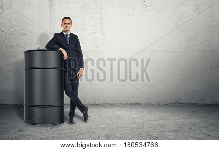 A businessman stands on a concrete floor leaning on a big grey barrel with serious face and a concrete wall behind him. Self-confidence in business. Business strategy. Hidden reserve.