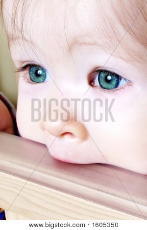 Baby Biting On Crib - Closeup Of Green Eyes