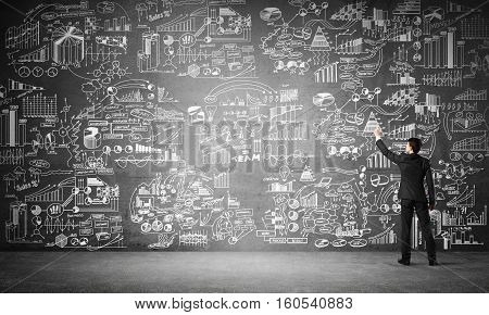 Back of businessman drawing business sketches on wall