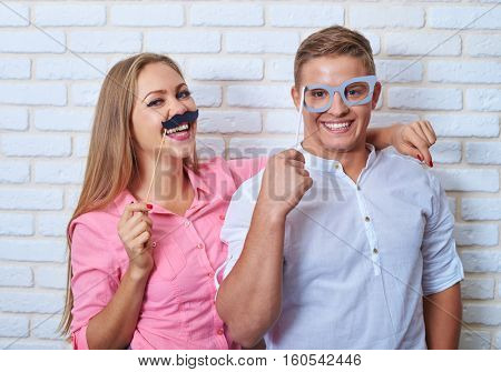 Mid shot of two funny lovers. They are extremely happy in a high spirits. Radiant with the joyful while holding paper sticks