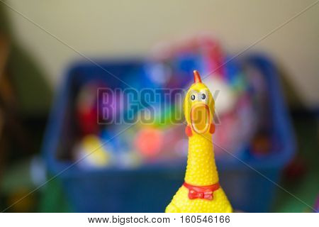 Toy rubber shriek yellow chicken on blur toy background in messy room kid room shallow DOF