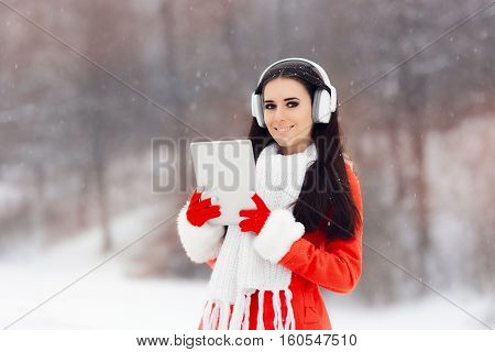Happy Winter Girl with Headphones and pc tablet