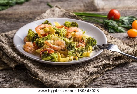 Pasta linguine with shrimps and broccoli in plate on wooden background. Top view.