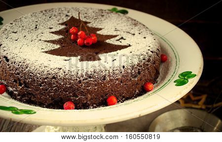 Traditional Homemade chocolate Christmas cake sprinkled with sugar powder, new year tree decoration with snow