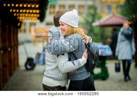 Eve of Christmas. Cute young couple has a good time at the Christmas bazaar. Young people stand in the middle of the fairground and joyfully embrace. Stall is festively decorated with shining garlands.