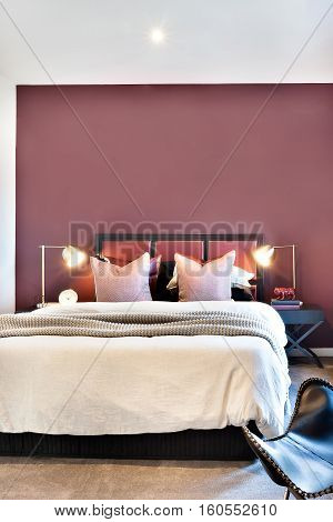 Luxury bed with flashing table lamps and lights beside a chair