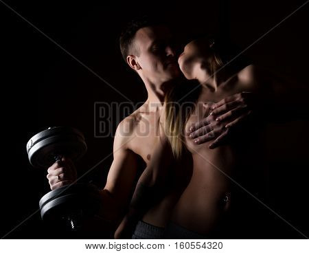 beautiful young sporty sexy couple showing muscle on a dark background.