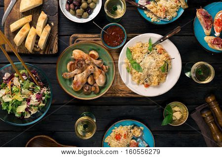 Italian risotto with cherry tomatoes basil and parmesan cheese roasted chicken legs snacks and wine on dark wooden table. Italian food table top view