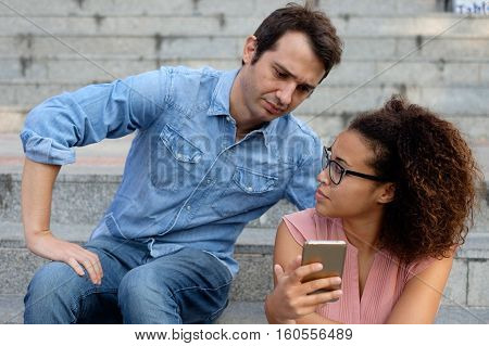 Man spying the mobile phone of her girlfriend