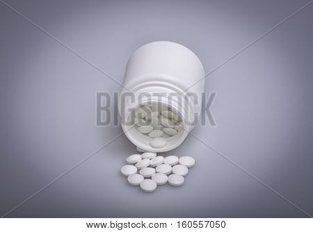 Heap of pills spilled out from plastic bottle isolated on the light blue background. Selective focus.