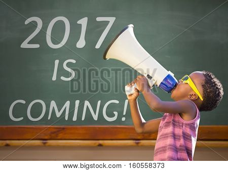 Boy with megaphone against 2017 new year sign on green board