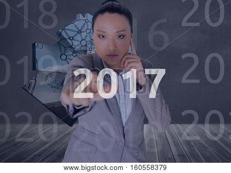 Portrait of business woman in 3D digitally generated background touching 2017 new year