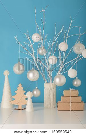 Vase in white knitted cover with white branches and Christmas toys. Christmas tree made of yarn and gifts.