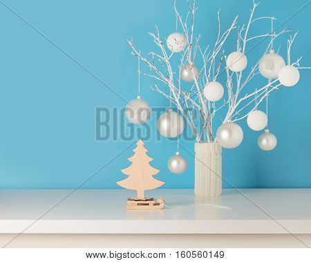 Vase in white knitted cover with white branches and Christmas toys. Tree on a sled.