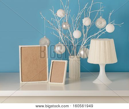 Vase in white knitted cover with white branches and Christmas toys. Empty wooden frame decorated with white yarn. Table lamp with knitted lampshade.