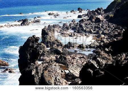Volcanic rock formation rising from the sea