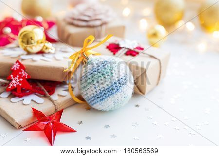 Christmas and New Year background with crocheted handmade ball presents and decorations for Christmas tree. Holiday background with stars confetti and light bulbs. Place for text.