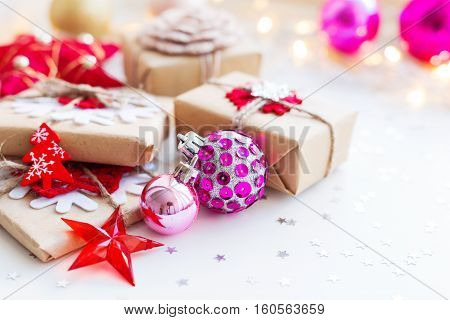 Christmas and New Year background with magenta purple decorative ball presents and decorations for Christmas tree. Holiday background with stars confetti and light bulbs. Place for text.