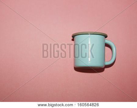 Blue metal cup on the pink background