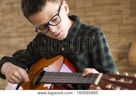 Boy With Glasses Playing Acoustic Guitar In Living Room