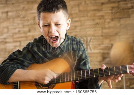 Young Boy Singing Out Loud While Playing Acoustic Guitar In Living Room